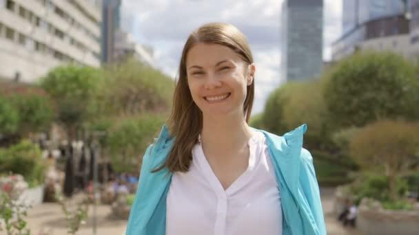 Podnikatelka v bílé košili v centru města. Při pohledu na fotoaparát. Profesionální žena s break