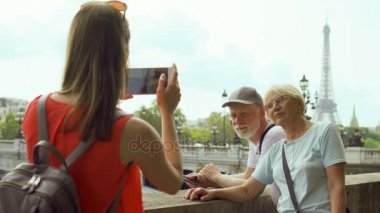 Daughter taking photo of senior parents on vacation trip in Paris. near Eifel Tower and river Seine