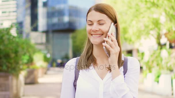 Smiling businesswoman in white shirt standing in downtown business dictrict talking on smartphone.