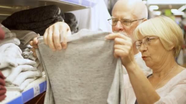Starší pár nakupovat v obchoďáku. Stojící vedle regálech s oblečením volba světle šedou vestu