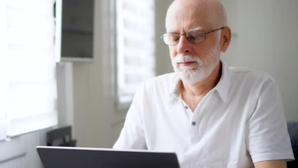 gestresster, übermüdeter älterer Herr in Weiß, der zu Hause am Laptop arbeitet. Reibt sich die schmerzenden Augen