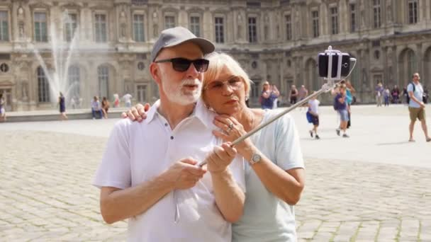 PARIS, FRANCE- CIRCA August 2017: Senior couple making selfie with smartphone on vacation in Paris