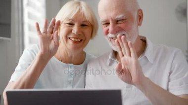 Senior couple sitting at home talking via messenger app Skype. Smiling waving hands in greeting