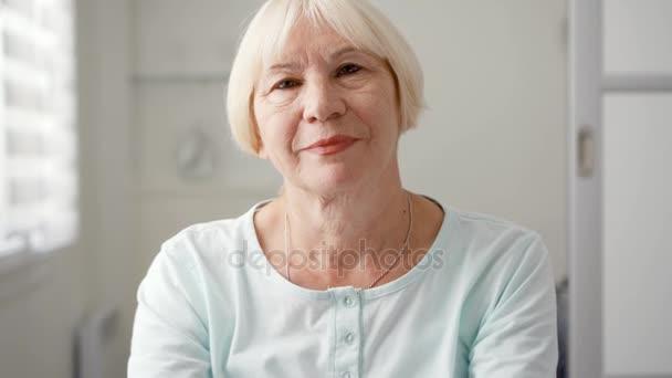 Porträt einer schönen älteren blonden Frau zu Hause. sitzt im weißen Wohnzimmer und schaut in die Kamera