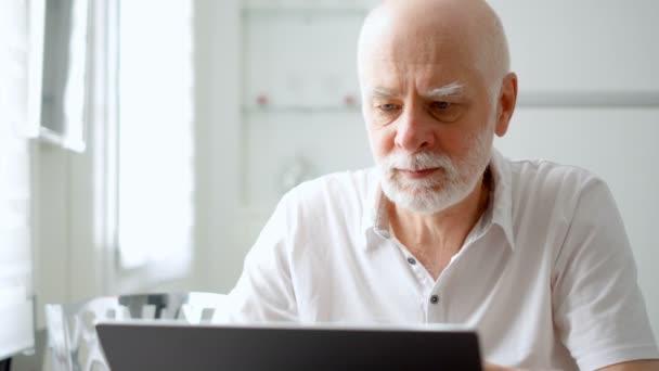 schöner älterer Herr, der zu Hause am Laptop arbeitet. Selbstständige Fernarbeit im Ruhestand