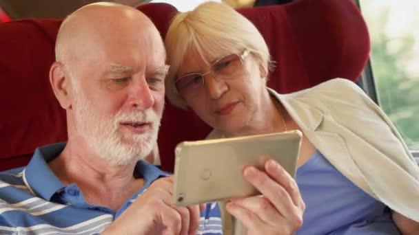 Vedoucí pár v rychlovlaku mezinárodního pomocí smartphonu. Aktivní moderní život po odchodu do důchodu