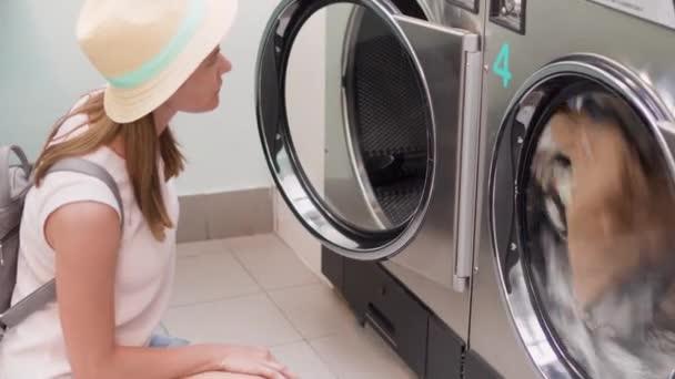 Mladá žena v klobouku v prádelně stroje. Sledování praní prádelny. Zaměřit se na podložku
