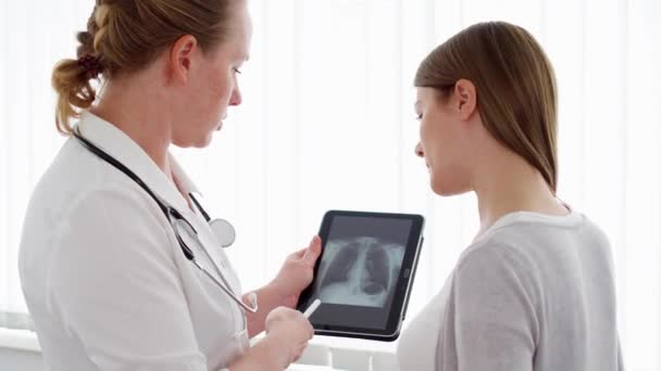 Woman physician showing X-ray on tablet to female patient in clinic. Female professional doctor at work
