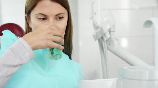 Woman patient in dental clinic. Rinsing out after teeth treatment. Dental equipment on background