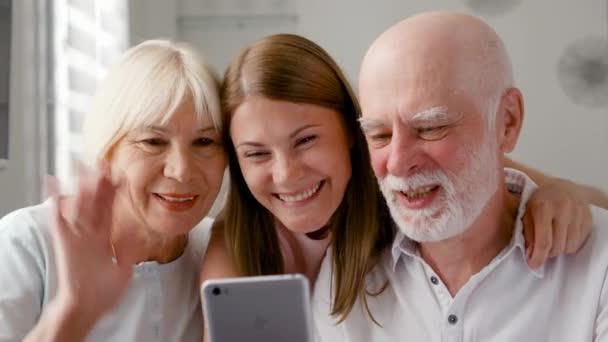 Starší pár a jejich dcera doma mluví přes messenger na mobilních zařízeních. Úsměv, smích