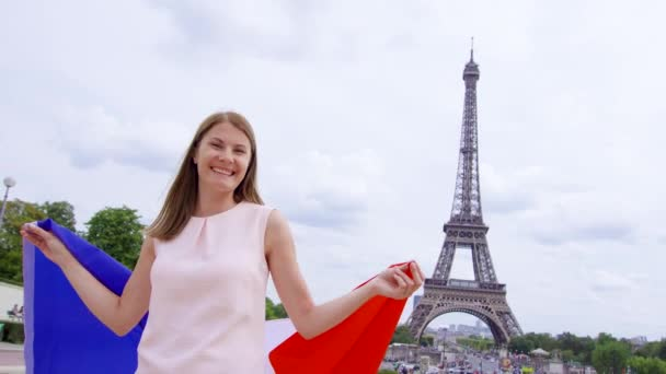 Woman with French flag near Eiffel Tower in Paris. Happy smiling tourist woman traveling in Europe.