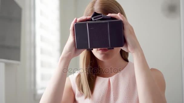 Giovane moderni graziosa donna utilizzando occhiali per realtà virtuale 360 Vr a casa. Futuro è concetto femminile