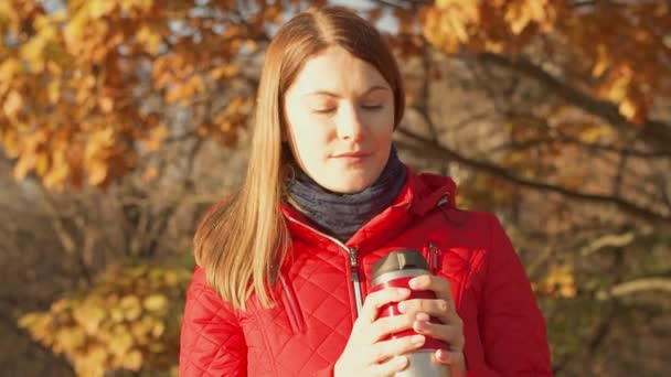 Boldog, mosolygós nő élvezi természet. Fiatal női piros kabátot forró bögre álló őszi parkban