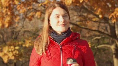 Happy Smiling Woman Enjoying Nature. Young female in red coat with hot mug standing in autumn park