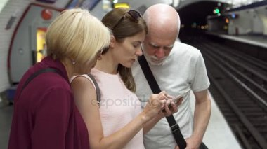 Senior couple and their daughter traveling by subway. Standing waiting for train, browsing in mobile
