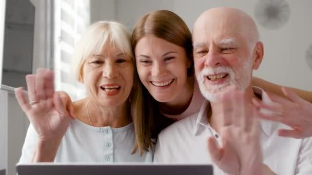 Starší pár a jejich dcera sedí u domů mluví přes messenger Skype. S úsměvem mává rukou