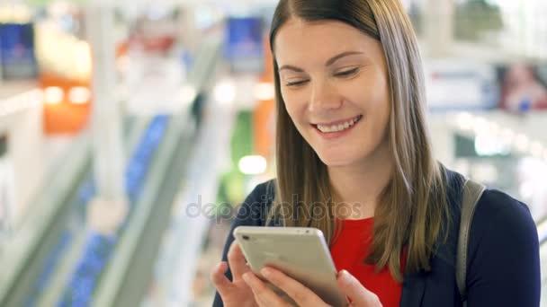 Fiatal gyönyörű nő bevásárlóközpont mosolyogva állt. Használja a smartphone, beszélgetett barátaival