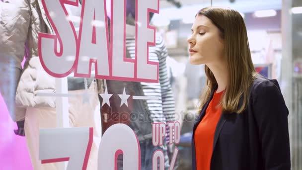 Gyönyörű vonzó fiatal nő állandó ablak shop közelében. Eladó jele. Női nézett ablak Webáruház