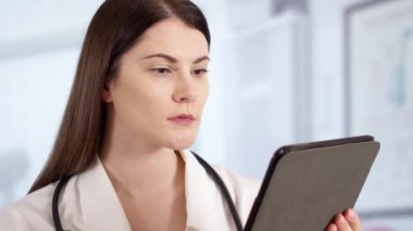 Professional female doctor with stethoscope in hospital room using tablet. Woman physician at work