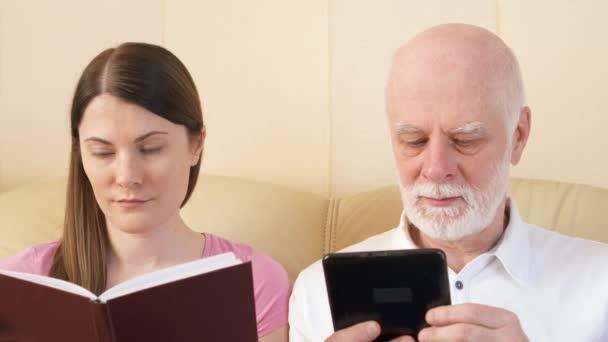 Otec a dcera, čtení e knih a tisku knihy. Koncept papíru vs digitální čtení