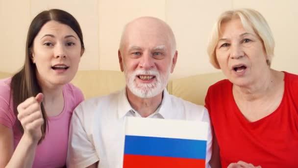 Senioři a dcera sledovat fotbalový zápas. Ruští fanoušci slaví vítězství v šampionátu