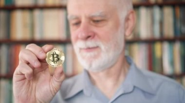 Senior man holding and looking at cryptocurrency bitcoin. Shiny virtual money of online trade