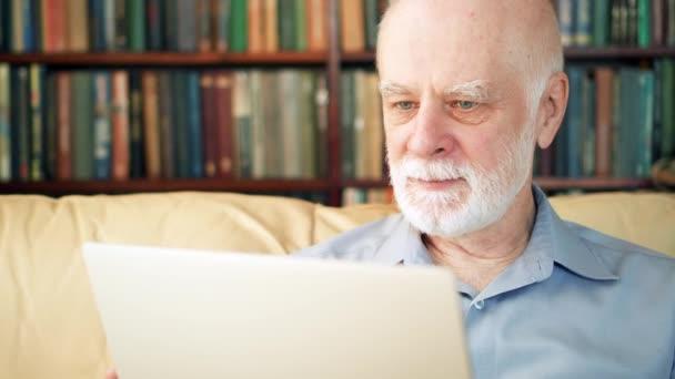 schöner älterer Herr, der zu Hause am Laptop arbeitet. erhalten gute Nachrichten aufgeregt und glücklich