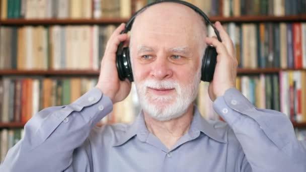 Veselý senior muž poslech hudby s bezdrátovými sluchátky. Důchodce meloman tanec na hudbu