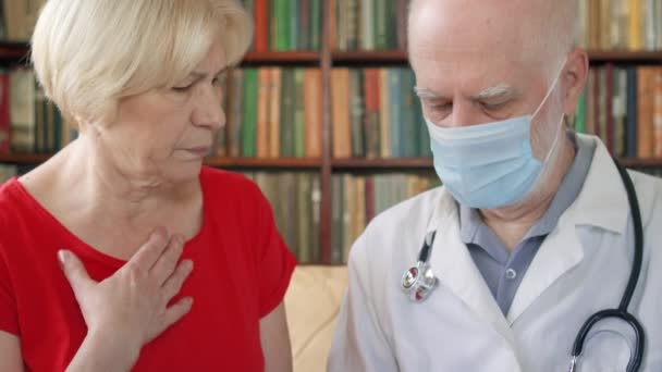Male professional doctor at work. Senior physician measuring temperature to patient by thermometer