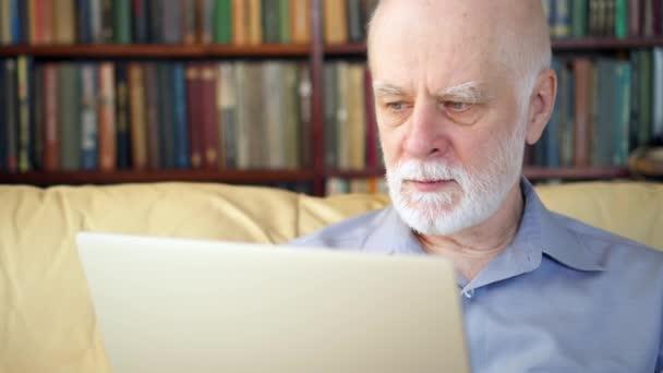 gestresster, übermüdeter älterer Herr in Weiß, der zu Hause am Laptop arbeitet. Schlechte Nachrichten verärgert
