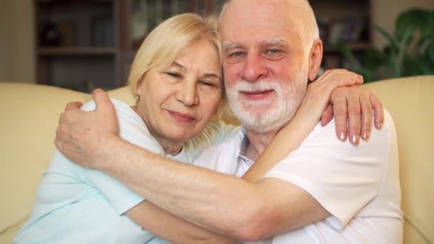 Portrét důchodci starší pár sedí na pohovce v domácí objímání. Koncept nikdy nekončící velká láska