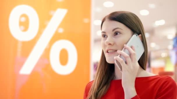 A nő shop ablak közelében. Eladó százalékjelet. Női shopper beszélünk telefonon barátjával értékesítés