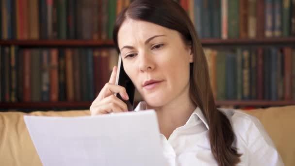 Podnikatelka práce s dokumenty doma. Profesionální žena mluví o mobilní telefon s kolegou