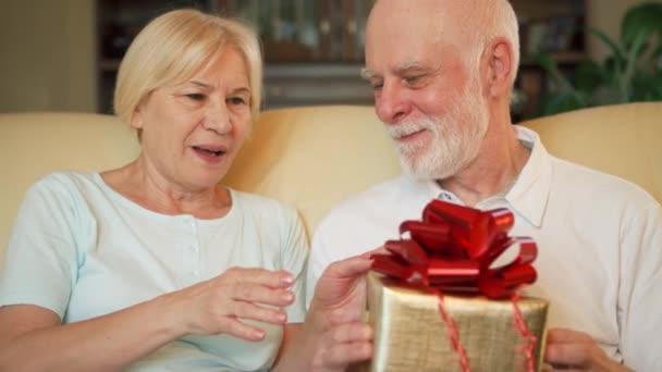 Uomo maggiore che dà il contenitore di regalo dorato presente anniversario compleanno alla moglie. Celebrazione di giorno di San Valentino