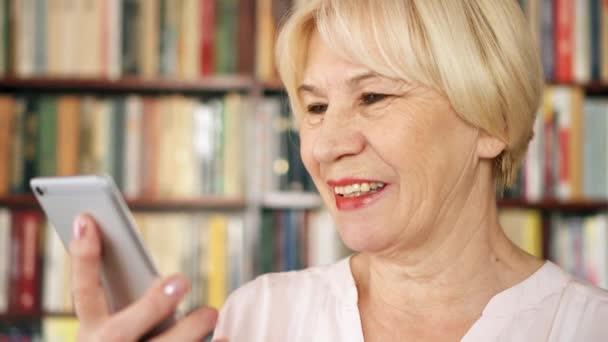 Moderní senior ženy doma mluvit přes aplikaci messenger v knihovně. Knihovna knihovna v pozadí