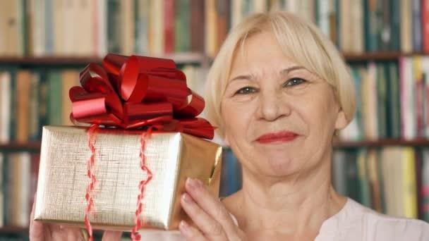 Starší žena s dárek. Důchodce drží zlatá Dárková krabice s červenou stužkou slaví narozeniny