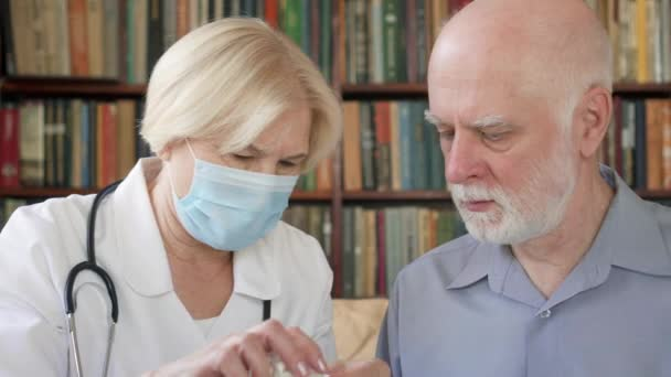 Female professional doctor at work. Senior woman physician treat senior male patient giving flu pill