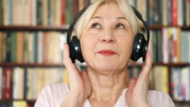 Cheerful senior woman listening music with wireless headphones. Pensioner meloman dancing to music