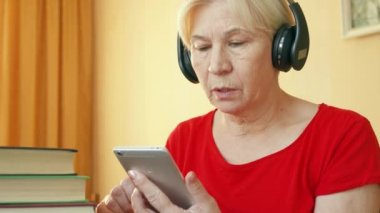 Senior woman uses application for listening skills training, learning foreign language on smartphone