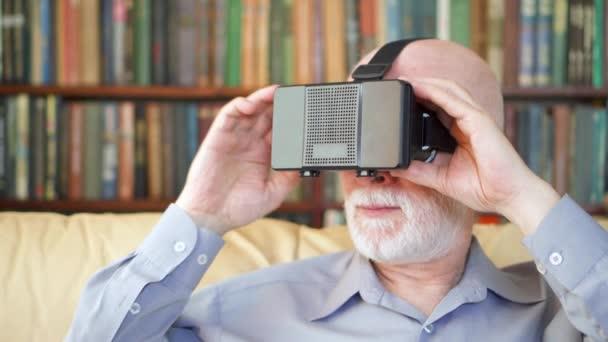 Starší muž pomocí Vr 360 brýle doma. Aktivní moderní starších lidí. Regály v pozadí