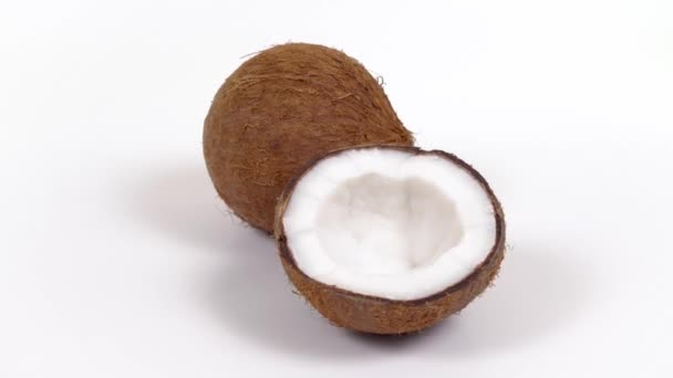 Whole coconut and half with yummy pulp rotating on white isolated background. Loopable seamless coco