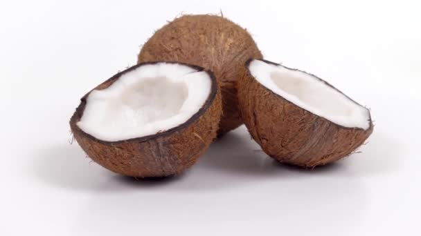 One whole coconut and two halves with yummy pulp rotating on white isolated background. Loopable seamless