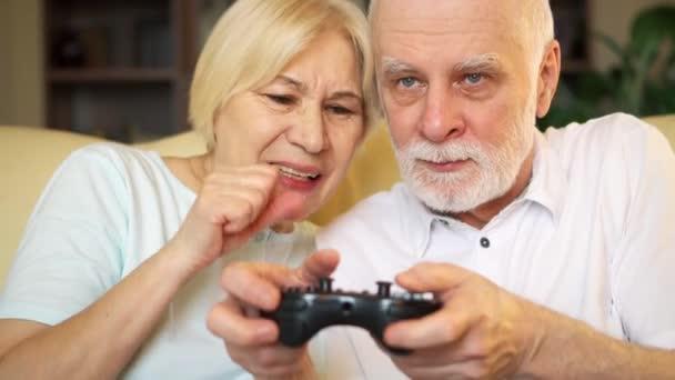 Idősebb pár vad játék video játékok otthon. A játékosok a játék konzol távirányító