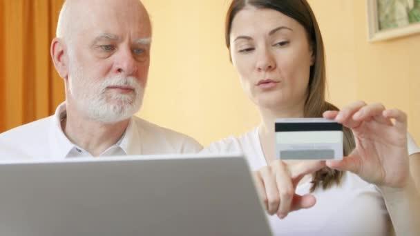 Senior Vater und seine kleine Tochter mit Smartphone zu Hause. Einkaufen mit Kreditkarte am Handy
