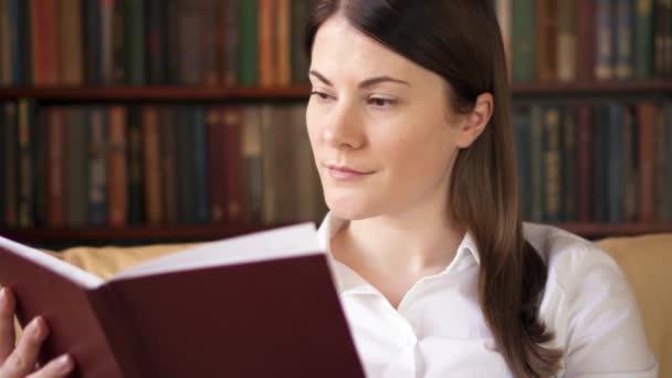 Mladá žena doma čtení tisku knihy. Koncept staré tradiční klasické papírové čtení
