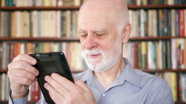 Elderly senior man relaxing at home reading e-book enjoying retirement. Bookshelves in background