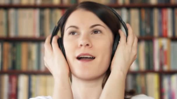 Happy female college student in university library listening music with big wireless headphones