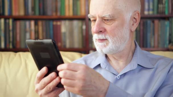 Starší starší muž relaxační doma čtení e knihy těší do důchodu. Regály v pozadí