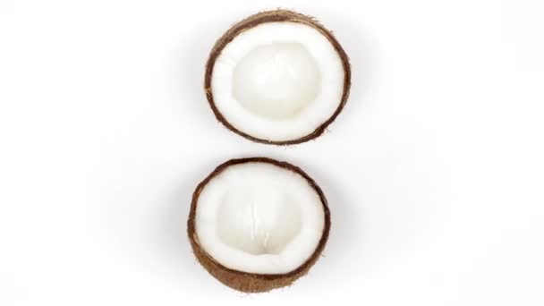 Two ripe coconut halves with yummy pulp rotating on white isolated background. Loopable seamless