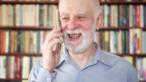 Modern senior man at home talking on cellphone in library. Bookcase bookshelves in background